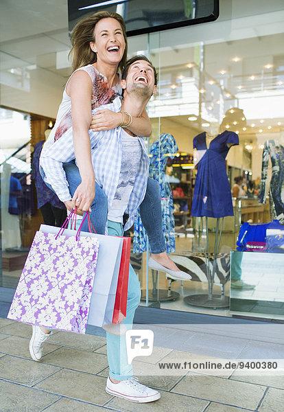 Mann mit Freundin Huckepack vor dem Bekleidungsgeschäft