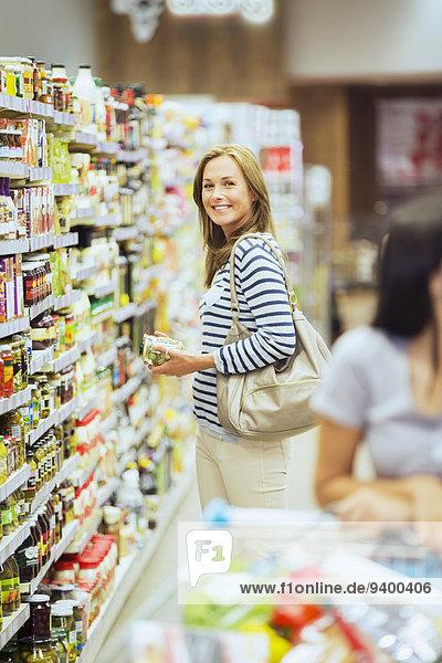 Lächelnde Frau beim Einkaufen im Lebensmittelladen