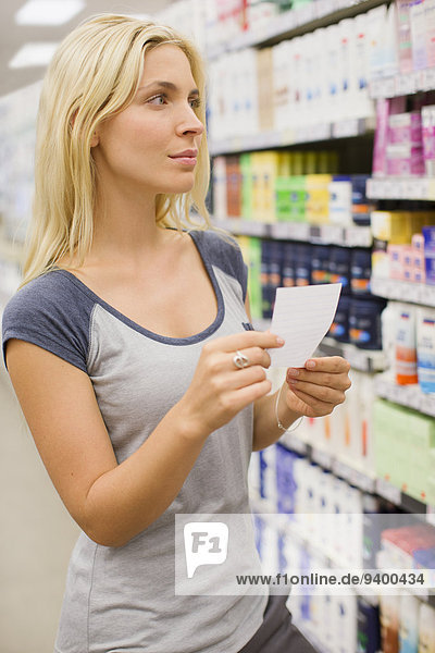 Woman reading shopping list in grocery store