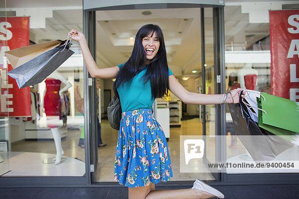 Frau trägt Einkaufstaschen vor dem Bekleidungsgeschäft