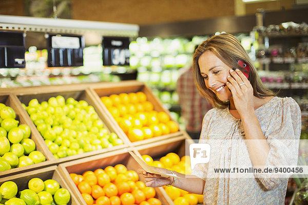 Frau spricht am Handy beim Einkaufen im Lebensmittelgeschäft