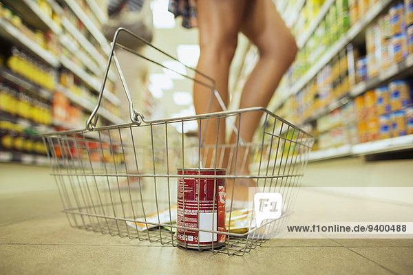 Close up of shopping basket with can of soup and flavor packets in grocery store