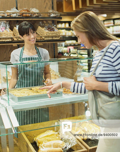 Frau beim Einkaufen an der Feinkosttheke im Lebensmittelgeschäft