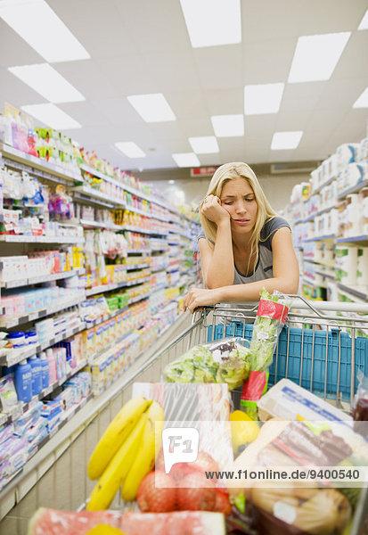 Gelangweilte Frau schiebt vollen Einkaufswagen im Lebensmittelladen