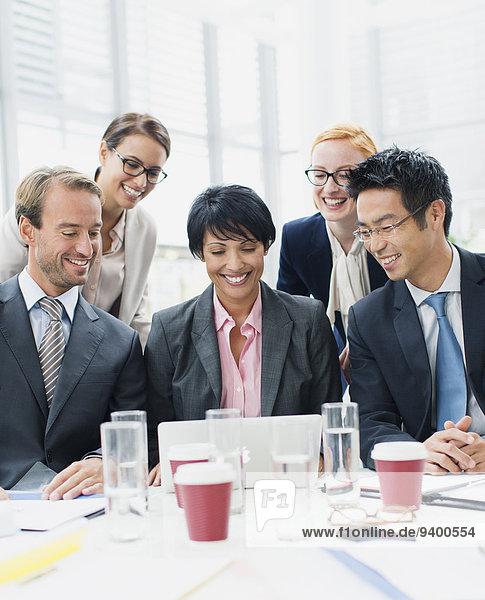 Business-Leute suchen Laptop in der Sitzung