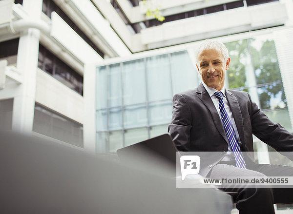 Geschäftsmann mit Laptop im Bürogebäude