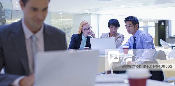 Geschäftsleute versammelten sich um den Laptop im Bürogebäude