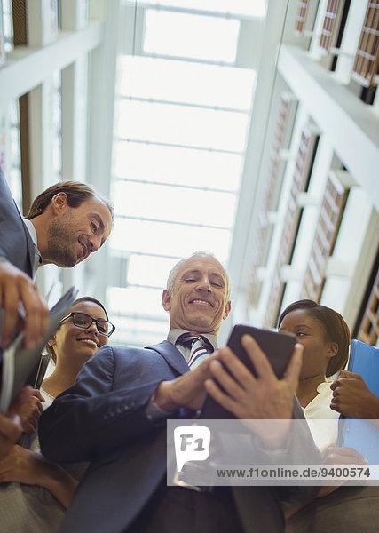 Geschäftsleute  die ein digitales Tablett in der Bürolobby betrachten