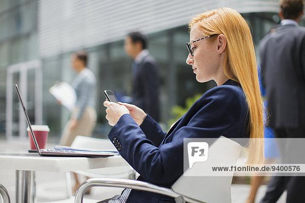 Geschäftsfrau mit Handy am Tisch im Freien
