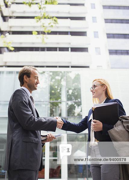 Geschäftsleute beim Händeschütteln vor dem Bürogebäude