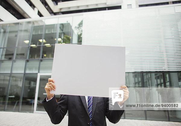 Geschäftsmann mit Urkunde im Bürogebäude