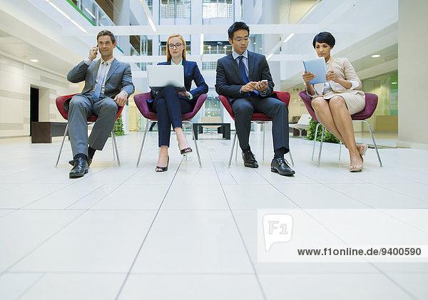 Geschäftsleute saßen in Stühlen und arbeiteten im Bürogebäude.