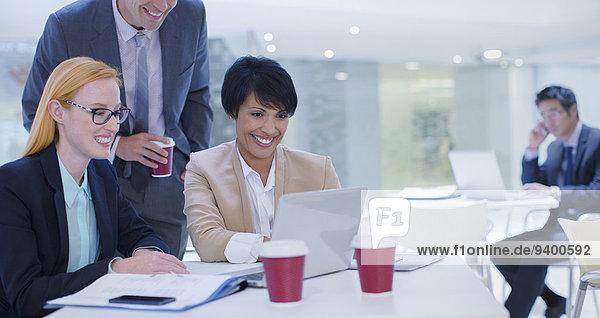 Geschäftsleute  die am Laptop am Tisch arbeiten