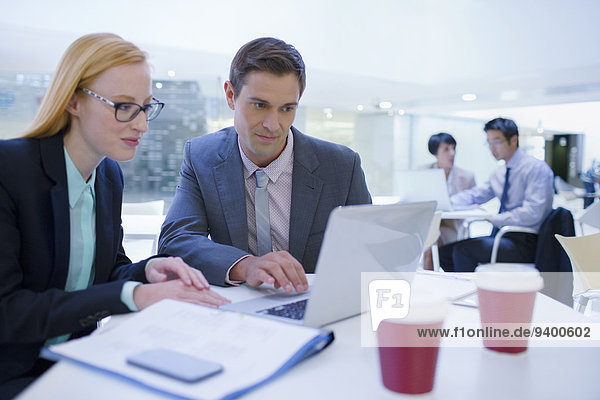 Geschäftsleute, die an Laptops am Tisch arbeiten