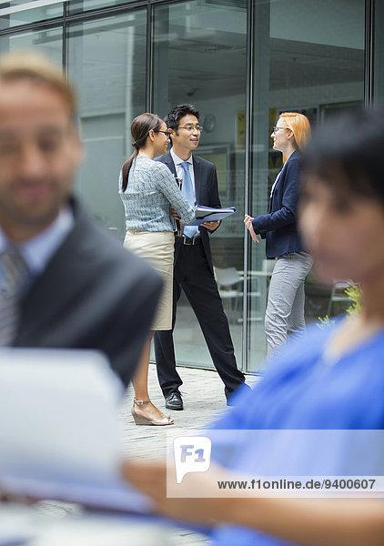 Geschäftsleute sprechen außerhalb des Bürogebäudes