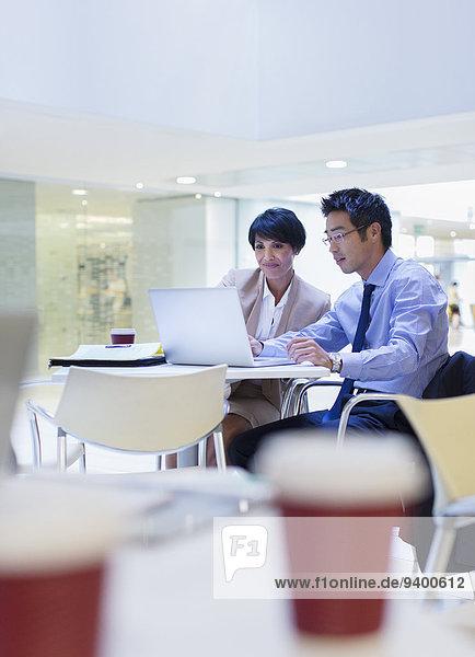 Geschäftsleute mit Laptop am Tisch
