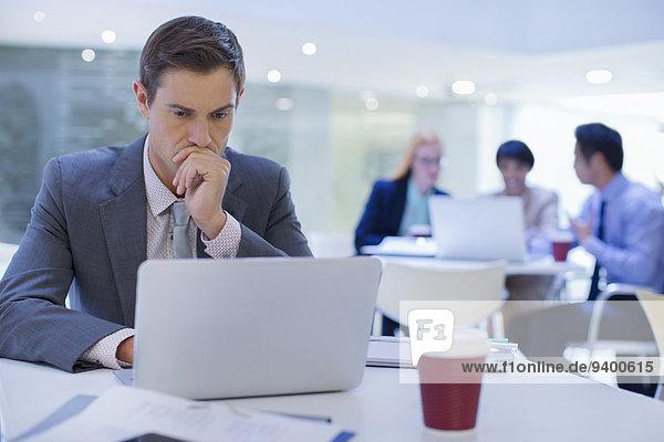 Geschäftsmann bei der Arbeit am Laptop am Tisch