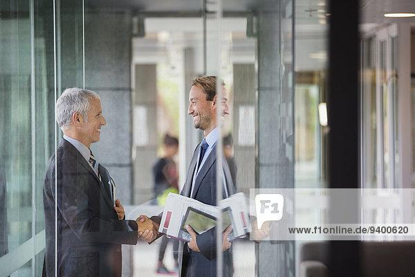 Geschäftsleute beim Händeschütteln im Bürogebäude