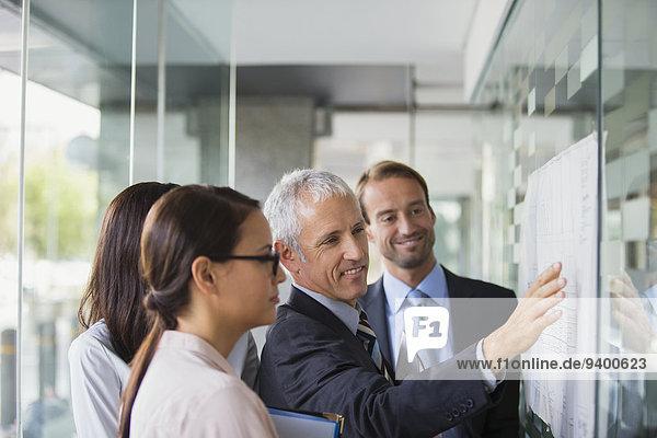 Geschäftsleute diskutieren Dokumente im Bürogebäude