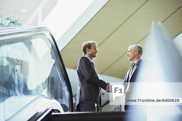 Geschäftsleute beim Händeschütteln oben auf der Treppe des Bürogebäudes