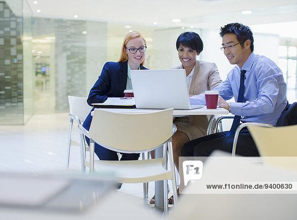 Geschäftsleute versammelten sich um Laptop im Bürogebäude Cafe