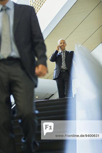 Geschäftsmann im Gespräch auf dem Handy auf der Rolltreppe im Büro