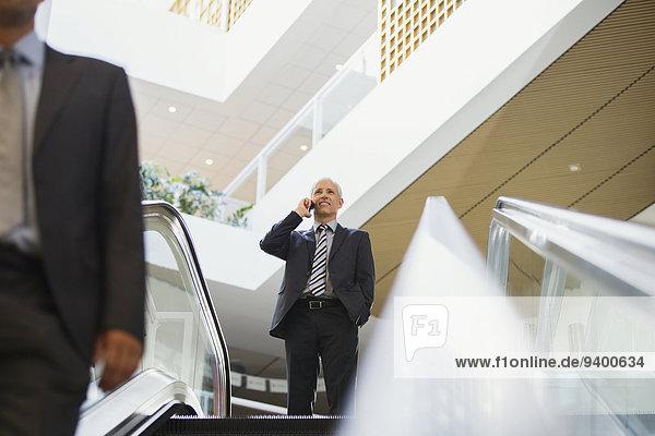 Geschäftsmann im Gespräch auf dem Handy oben an der Treppe im Bürogebäude