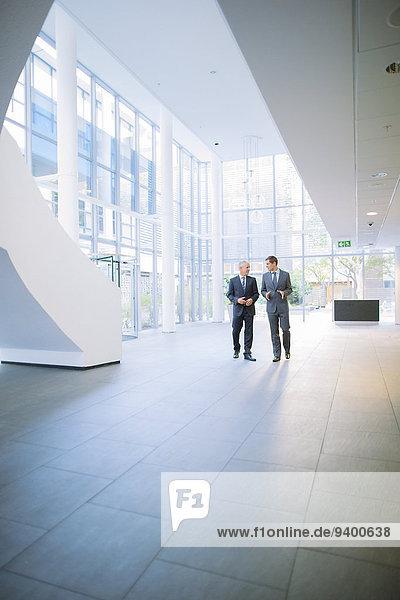 Geschäftsleute  die gemeinsam im Bürogebäude spazieren gehen
