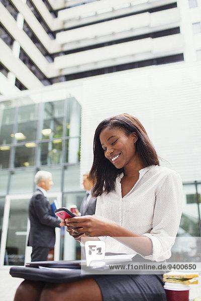 Geschäftsfrau auf der Bank sitzend mit dem Handy im Freien