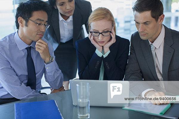 Geschäftsleute versammelten sich um den Laptop am Tisch im Bürogebäude.