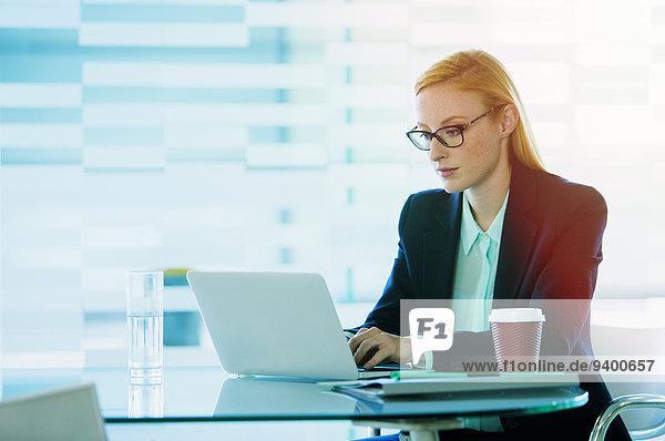 Geschäftsfrau bei der Arbeit am Laptop im Bürogebäude Cafe