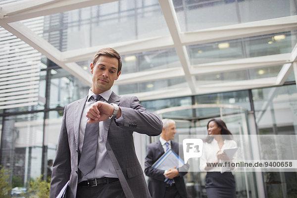 Geschäftsmann auf der Suche nach einer Uhr  die das Bürogebäude verlässt.