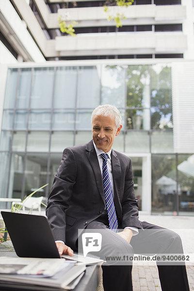 Geschäftsmann mit Laptop auf der Bank vor dem Bürogebäude