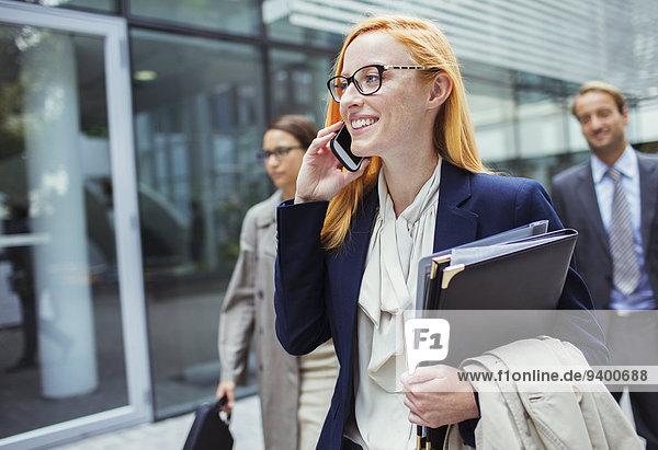 Geschäftsfrau beim Telefonieren vor dem Bürogebäude