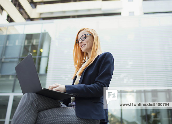 Businesswoman working on laptop outside office building