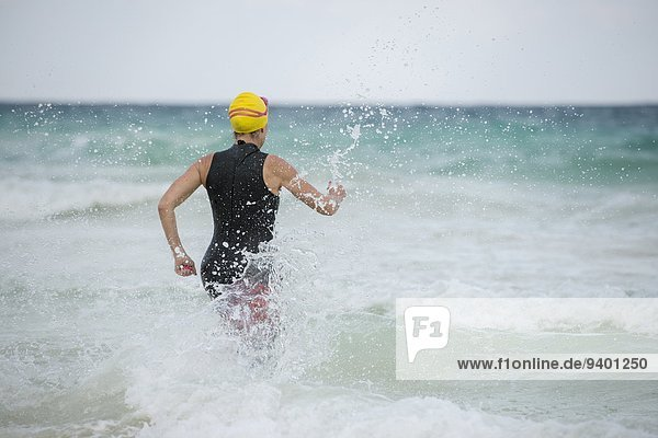 A swimmer running to the ocean in Tulum  Mexico.