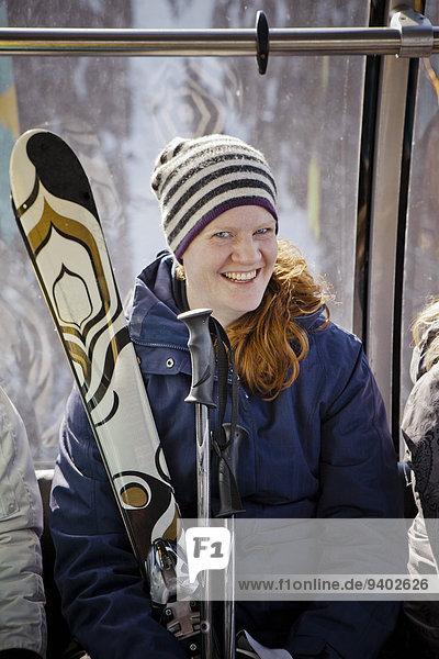 A female skier on gondola on Whistler Mountain.