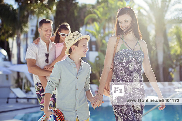Familie mit zwei Kindern  die am Swimmingpool spazieren gehen