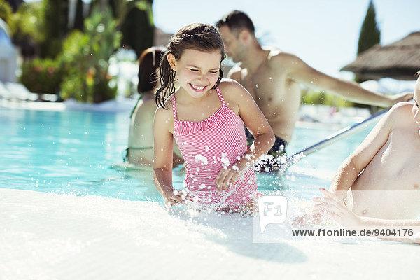 Glückliche Kinder spritzen Wasser im Schwimmbad