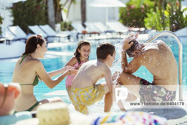 Verspielte Familie mit zwei Kindern am Pool