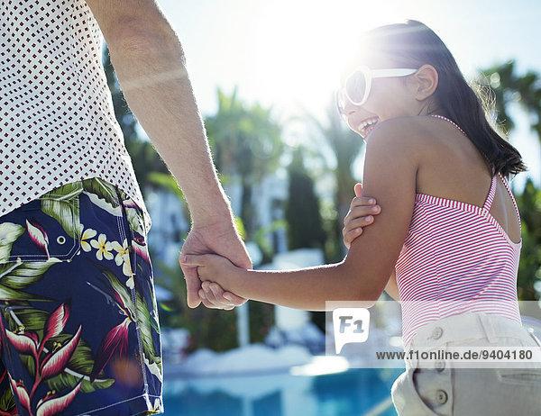 Rückansicht von Vater und Tochter beim Händchenhalten am Schwimmbad