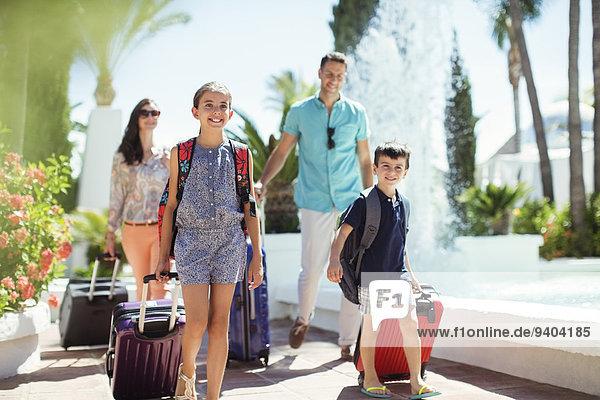 Familie mit Koffern am Springbrunnen vorbei im Ferienort