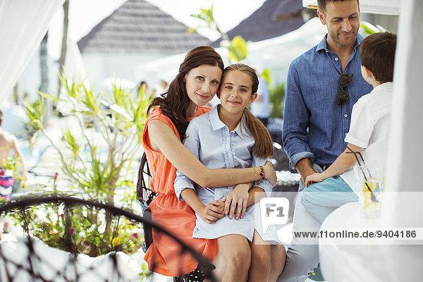 Eine glückliche Familie mit zwei Kindern  die sich im Poolbereich des Resorts entspannen.