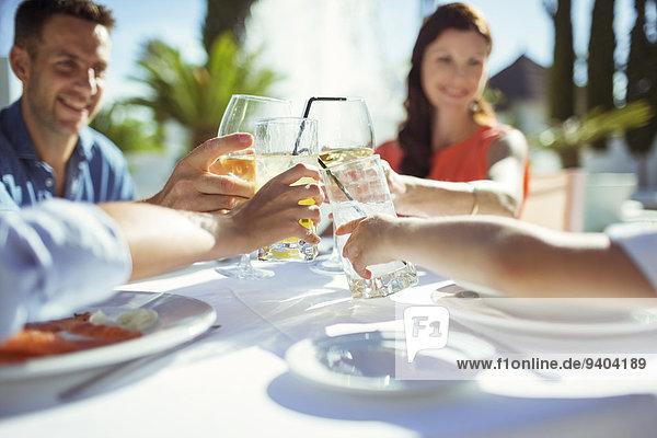 Freunde, die bei Tisch im Freien anstoßen