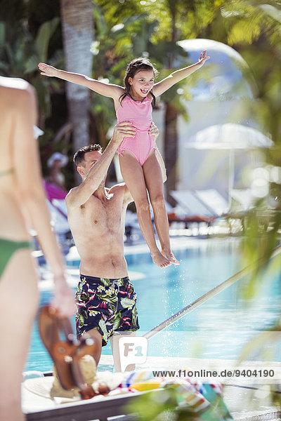 Vater hebt lächelnde Tochter am Swimmingpool auf