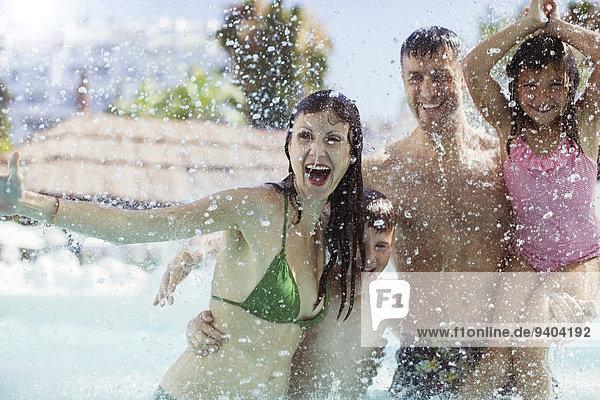 Familie mit zwei Kindern beim Planschen und Lachen im Schwimmbad