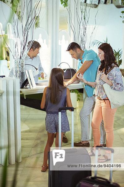 Familie mit Tochter an der Rezeption in der Hotellobby