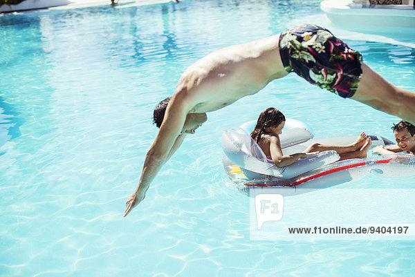 Mann taucht ins Schwimmbad, Kinder schwimmen auf Luftmatratze im Hintergrund