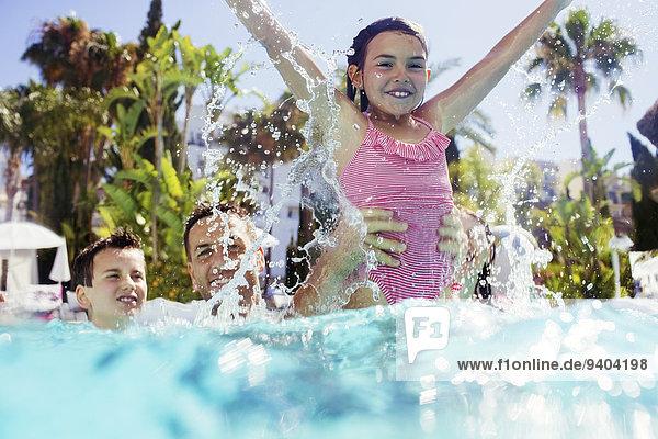 Vater spielt mit Sohn und Tochter im Schwimmbad