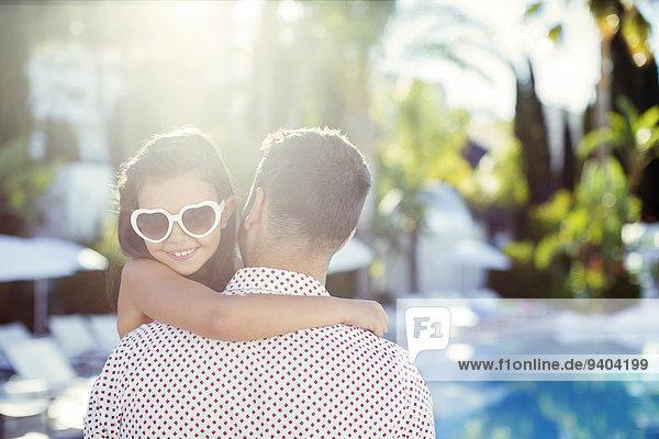 Vater tragende Tochter mit herzförmiger Sonnenbrille am Schwimmbad